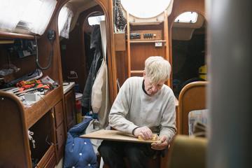 Sweden, Senior man polishing wood