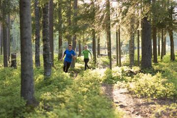 Sweden, Vasterbotten, Grossjons Nature Reserve, Man and woman running in forest