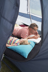 Sweden, Father and daughter (2-3) lying down in tent