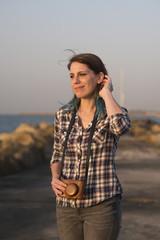 Israel, Tel Aviv, Woman in plaid shirt with analog camera