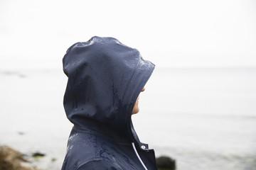 Sweden, Gotland, Mature woman in hood at beach