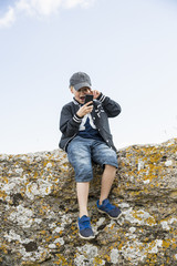 Sweden, Gotland, Boy (8-9) sitting at edge of cliff and using telephone