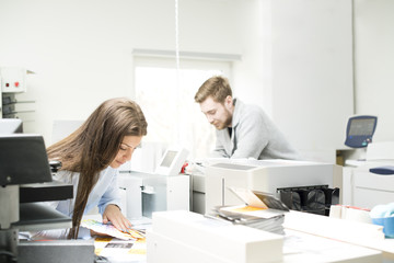 Sweden, Coworkers looking at printouts in office