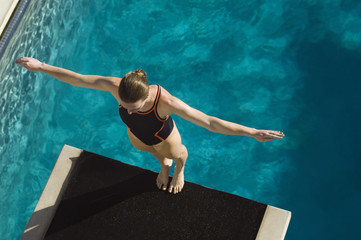 High angle view of a female swimmer ready to dive while standing at the edge of the springboard