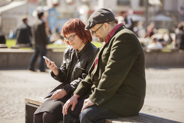 Sweden, Sodermanland, Woman with down syndrome sitting on bench and checking smart phone together with boyfriend
