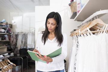 Sweden, Mature woman writing in notebook in clothes store