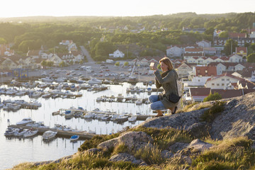 Sweden, Gotaland, Bohuslan, Grebbestad, Mid adult woman taking pictures from rock overlooking port and bay