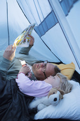 Sweden, Father and daughter (4-5) reading comic book in tent