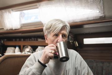 Sweden, Senior man drinking from tin mug