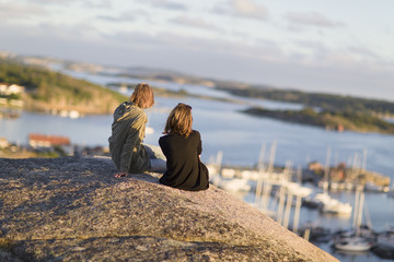 Sweden, Gotaland, Bohuslan, Grebbestad, Mid adult women sitting on rock overlooking port and bay