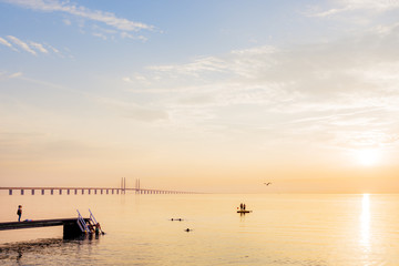 Scenic view of sea with Oresund bridge in background at sunset