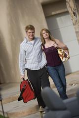 Caucasian couple with luggage walking toward car