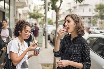Israel, Tel Aviv, Two women eating sweets in street