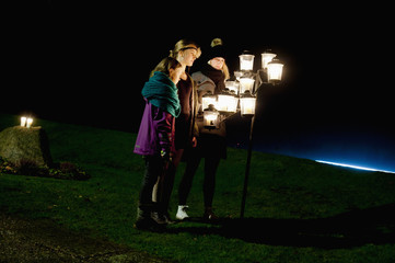 Sweden, Ostergotland, Clocklike, Sisters (8-9, 14-15) standing by hanging lanterns at night