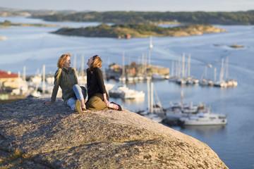 Sweden, Gotaland, Bohuslan, Grebbestad, Mid adult women sitting on rock overlooking port and bay