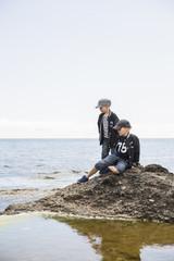 Sweden, Gotland, Boys (6-7, 8-9) on rock in sea