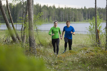 Sweden, Vasterbotten, Grossjons Nature Reserve, Man and woman running in forest