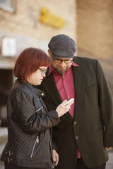 Sweden, Sodermanland, Woman with down syndrome checking smart phone together with boyfriend in street