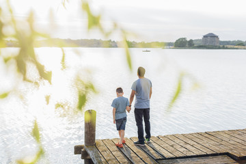 Sweden, Blekinge, Karlskrona, Father and son (8-9) by lake
