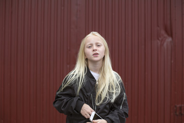 Sweden, Portrait of girl (12-13) holding mobile phone