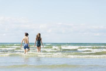 Sweden, Oland, Kopingsvik, Girl (10-11) and boy (8-9) walking into sea