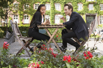 Sweden, Skane, Malmo, Young woman and man sitting at table and looking at smart phone