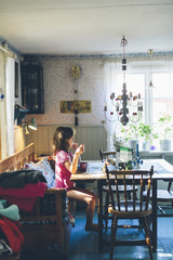 Sweden, Girl (8-9) sitting at table and eating