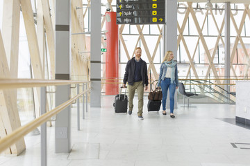 Sweden, Vasterbotten, Umea, Man and woman walking with suitcases through modern railway station