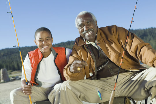 Portrait of happy grandfather and grandson fishing together