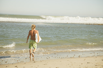 USA, California, Los Angeles, Venice, Man with surfing board walking on beach