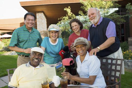 Group portrait of happy multiethnic people enjoying at a golf resort