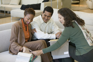 Couple Looking at fabric Swatches With Saleswoman in furniture store