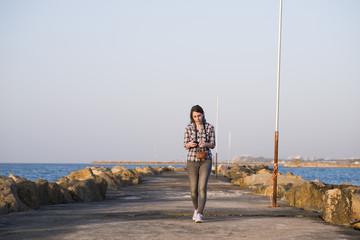 Israel, Tel Aviv, Woman walking on pier