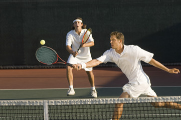 Young male tennis player hitting ball with doubles partner standing in background