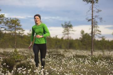 Sweden, Vasterbotten, Grossjons Nature Reserve, Woman running in meadow