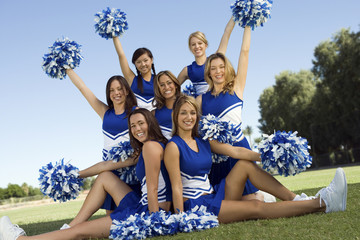 Portrait of confident cheerleaders holding pompoms on field