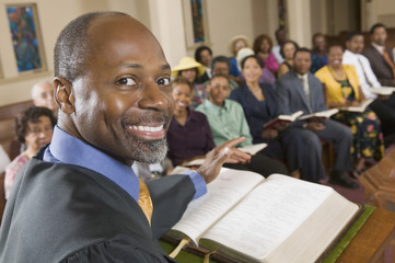 Preacher at altar with Bible preaching to Congregation portrait close up