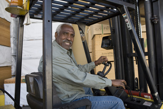 Portrait of a happy senior warehouse worker driving forklift