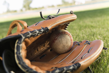 Extreme closeup of an old baseball glove and ball on the field