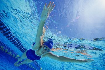 Middle aged female participant swimming under water in a swimming race