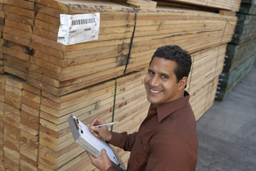 Portrait of middle aged man checking lumber in warehouse