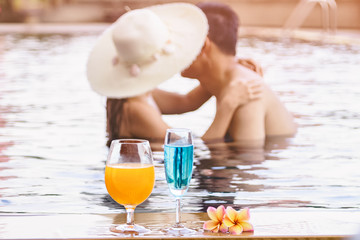 Romantic Asian couple kissing in the swimming pool with cocktail