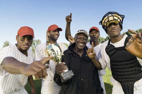 Portrait of baseball team and coach with trophy celebrating victory outdoors
