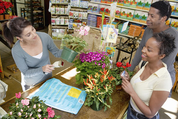 African American couple buying flower plant from store