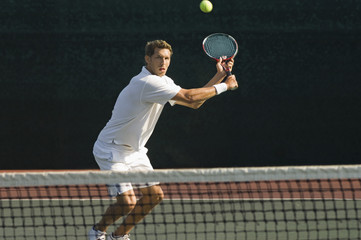 Male tennis player hitting backhand by net on the tennis court