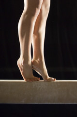 Foto op Aluminium Gymnastiek Closeup low section of a female gymnast on balance beam against black background