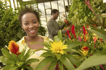 Portrait of a happy African American woman with man in background at botanical garden