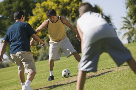Boy (13-15) with two young men playing soccer outdoors in park.