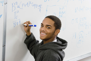 Portrait of smiling male student solving algebra equation on whiteboard in classroom