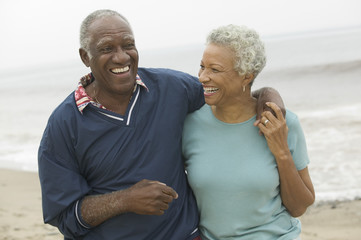 Cheerful African American mature couple with arms around at the beach